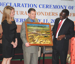 Prime Minister Mizengo Pinda (right) presenting a photograph depicting wildebeest migration in the Serengeti to the President and Founder of Seven Wonders, Dr. Philip Imler at the Mount Meru Hotel on February 11. Left is Dr. Imler's wife, Nancy Imler. (Photograph by Filbert Rweyemamu)