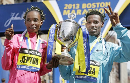 Rita Jeptoo of Kenya and Lelisa Desisa of Ethiopia pose with a trophy at the finish line after winning the women's and men's divisions of the 2013 Boston Marathon in Boston Monday, April 15, 2013. (photo: AP)