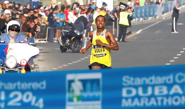 Tsegaye Mekonnen Asefa of Ethiopia, touching the finishing line during the Standard Chartered Dubai Marathon at Umm Suqeim Road in Dubai on Friday,  January 24, 2014. KT photo by Juidin Bernarrd