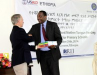 Mr. Dennis Weller, USAID Ethiopia Mission Director, handed over a sample of the new reading curriculum textbooks to Ato Shiferaw Shigute, Minister of Education, at the READ Launching Ceremony. Photo Credit : USAID/READ TA