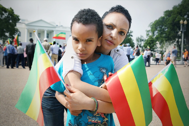 Near the White House on Friday, Serkalem Selassie and her 9-year-old son, Nafkot, protested President Obama's upcoming trip to Ethiopia. As a journalist in her homeland, she was jailed, and Nafkot was born while she was in prison. She has political asylum now. (Evelyn Hockstein/For The Washington Post)