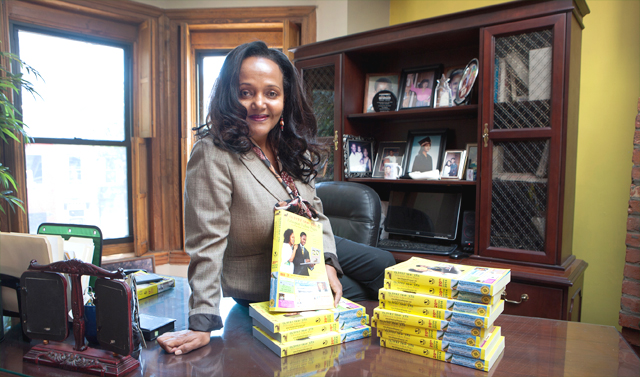 """Yeshimebeth """"Tutu"""" Belay, publisher of the Ethiopian Yellow Pages, displays her latest telephone directory. (David Peterson/State Dept.)"""