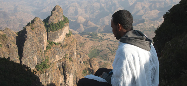 "Perched along the mountain's ledge, a young Ethiopian Orthodox monk overlooks the vast Simien Mountains — known as the ""Chess pieces of God.""(Photo: Nick Crane)"